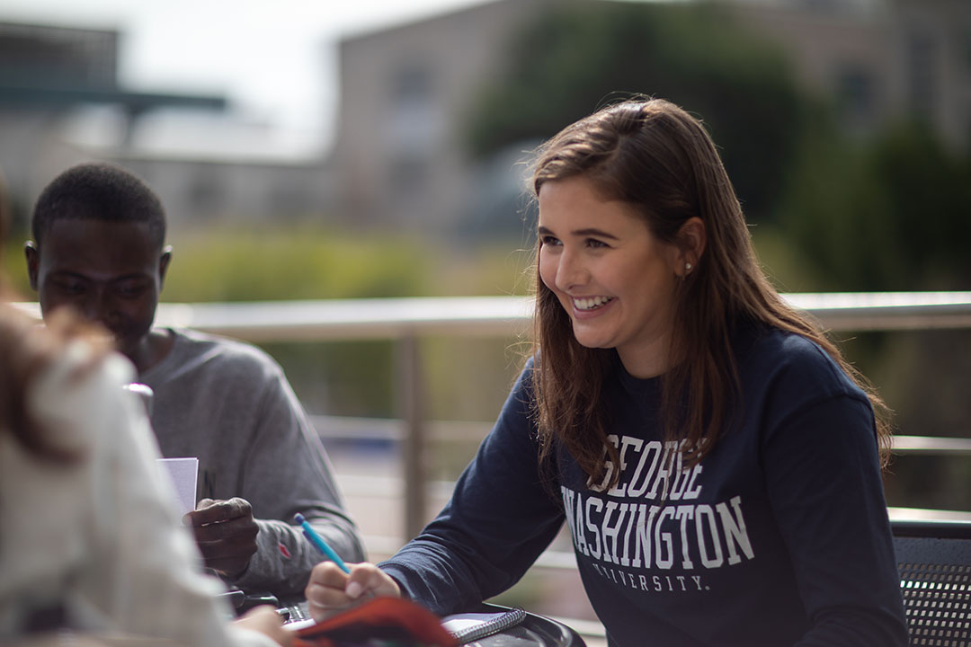 A student in a George Washington University sweatshirt sitting at a table