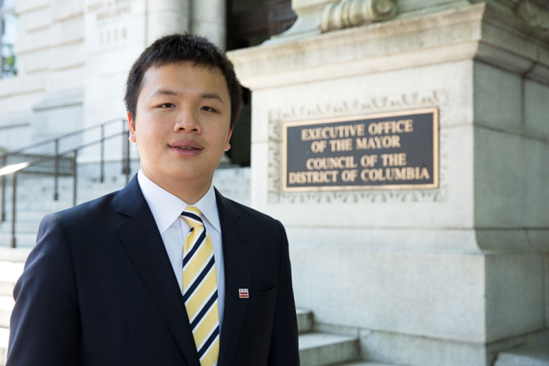 Matthew Jiang stands in front of the Executive Office of the Mayor building where he had an internship